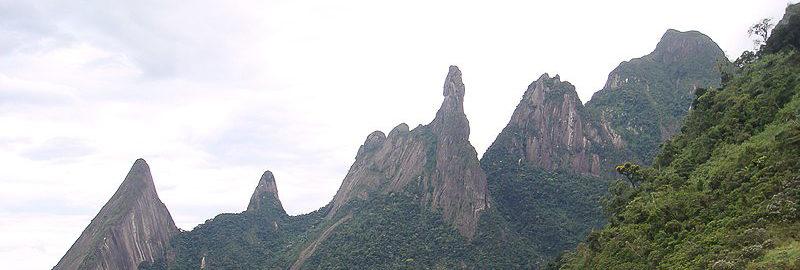 Três picos, o do meio em destaque e tem o contorno semelhante a uma mão apontando o dedo indicador para o céu
