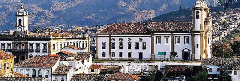 Imagem Aérea de Ouro preto onde fica em primeiro plano varias construção com arquitetura barroca e ao fundo