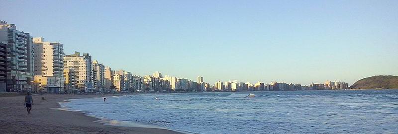 Um céu azul sob a praia com poucas pessoas caminhando e vários prédios ao redor.