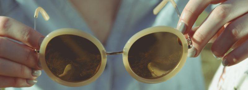um par de óculos em uma mão femina